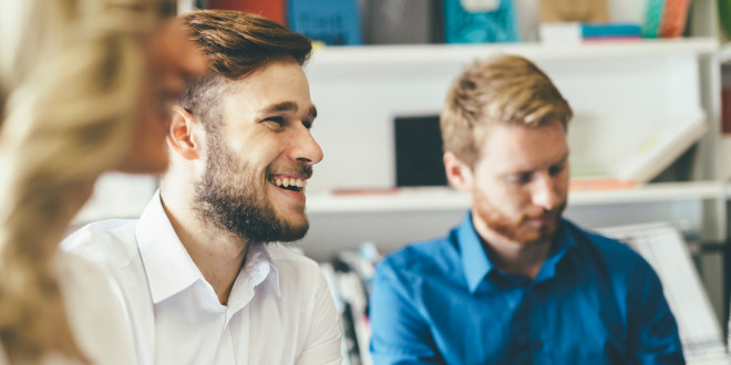 En mann sitter i en gruppe og smiler.