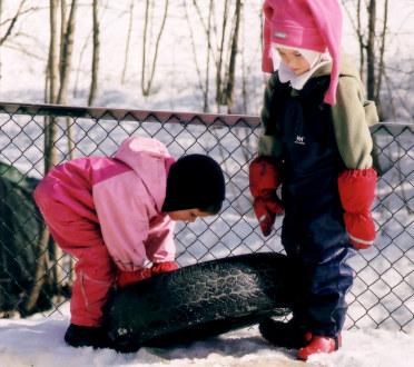To barnehagebarn leker med et bildekk
