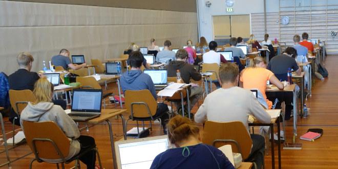 En stor gruppe sitter og skriver og jobber med eksamen.