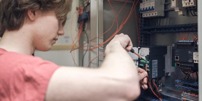 Elev på yrkesfag reparerer elektrisk skap.