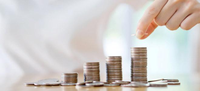 En hånd legger mynt på en stabel med mynter.