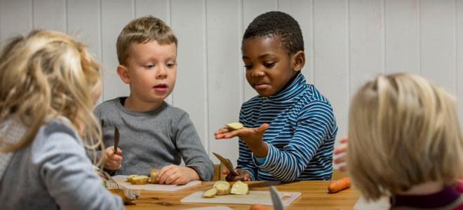 Fire barn sitter ved et bord og skjærer opp frukt.