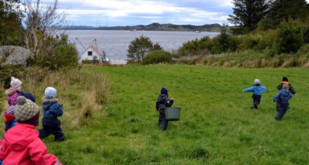 Barnehagebarn løper på en grønn eng med sjøen i bakgrunnen.