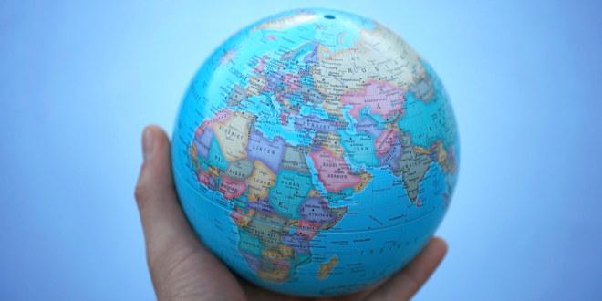 En hånd som holder en liten jordklode