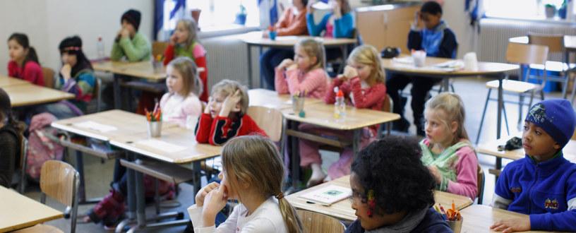 Elever i et klasserom ved hver sin pult