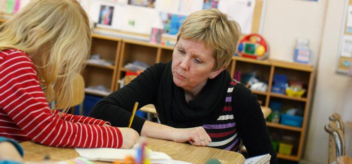 jente i barneskolen tegner sammen med lærer