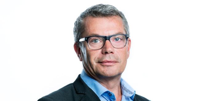 Mann med briller, grått hår, blå skjorte og svart dressjakke.