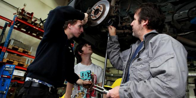 To gutter og en mann skrur på undersiden av en bil.