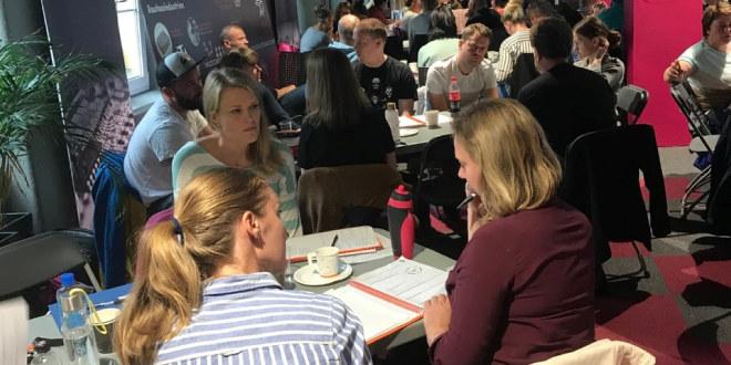 Tre damer sitter rundt et bord og diskuterer. I bakgrunnen er det mange andre voksne.