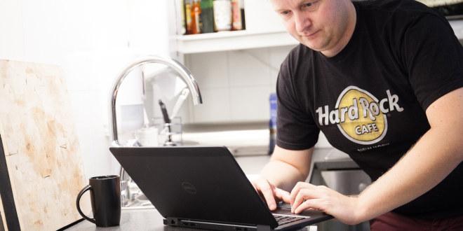 Mann som skriver på PC på kjøkkenbenken