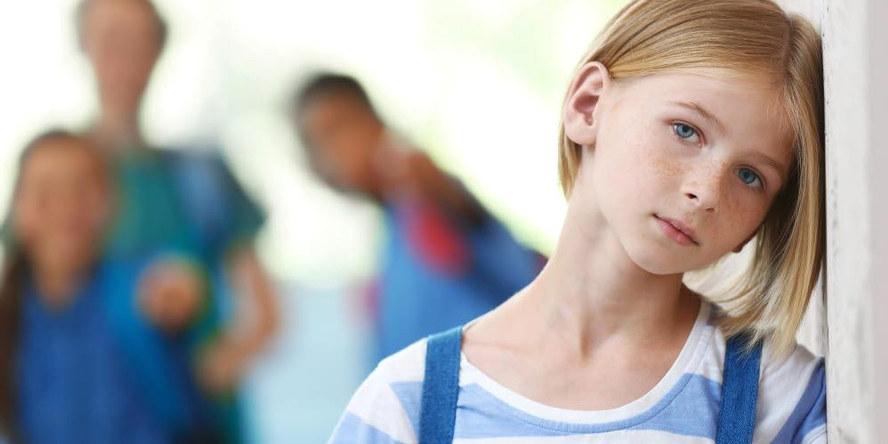 Bilde av et barn som ser inn i kamera med hodet hvilende på veggen. En skimter to personer i bakgrunnen.