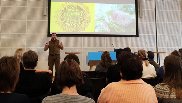 En mann står ved en presentasjon om blomster med mange hørere foran.
