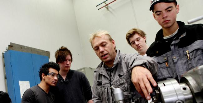 Fire gutter står rundt en lærer i et verksted. Han viser hvordan en maskin fungerer.