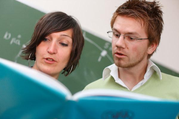En kvinne og en mann studerer samme bok i et klasserom foran en tavle