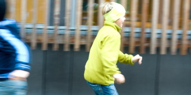 En liten gutt løper forbi en annen i skolegården.
