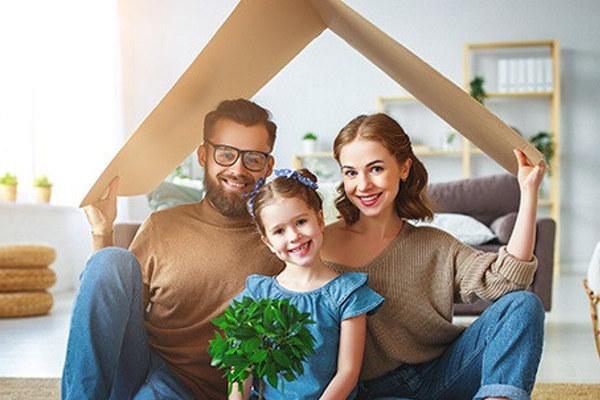 Familie med far, datter og mor sammen smiler i egen stue
