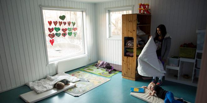 Voksen tar dyne over barn som skal sove inne i en barnehage