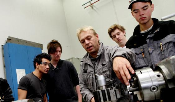 Elever på yrkesfag står rundt en lærer som demonstrerer bruk av en motor