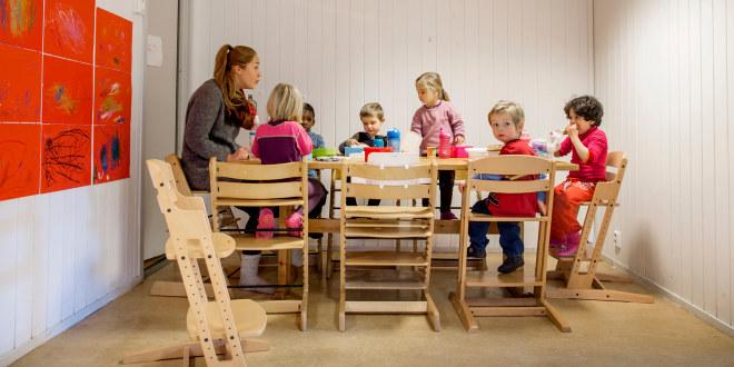 Barnehagebarn sitter rundt et bord og spiser sammen med en voksen.