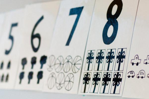 Tallene 5, 6, 7 og 8 vises på ark på en vegg.