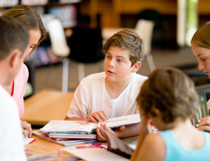 Elever og lærer sitter rundt et bord og snakker sammen. På bordet ligger mange skolebøker