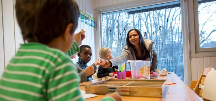 barn sitter rundt et bord. En kvinnelig barnehagelærer gir et av barna et fargestift