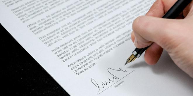 Nærbilde av hånden til noen som signerer en avtale