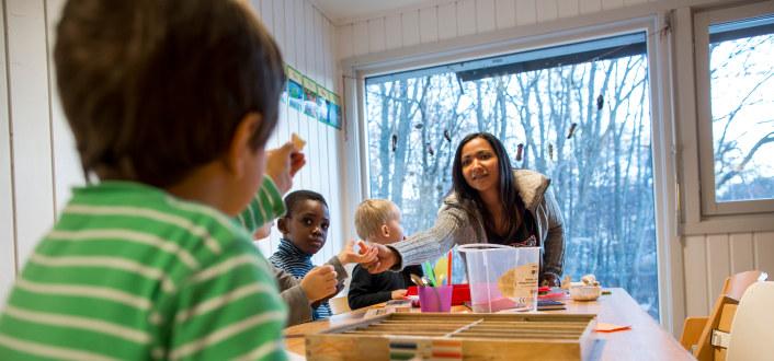 barnehagebarn sitter rundt et bord og jobber med tegninger. Barnehagelærer gir fargestift til en av barna.