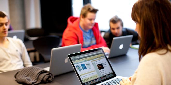 Fire ungdommer sitter rundt et bord og jobber på PC-en.