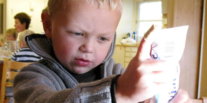 Gutt ved matbordet i barnehagen klemmer kaviar ut av en tube