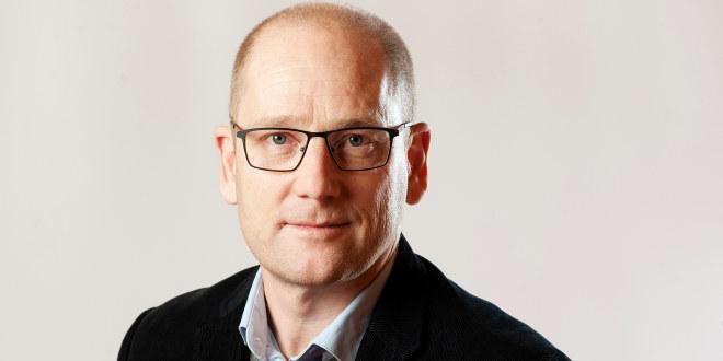 Skallet mann med briller. Blå skjorte inni grå genser og svart dressjakke.