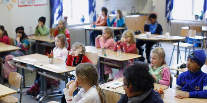 Barn sitter ved pultene sine i et klasserom.
