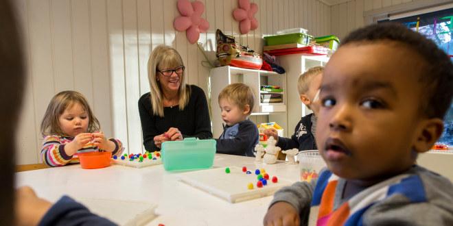 Fire  små barn og en barnehagelærer sitter rundt et bord og leker.