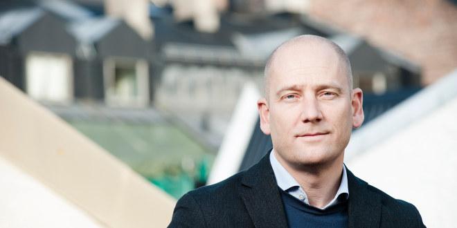 Steffen Handal står på et tak og halvsmiler, ikledd en dressjakke.