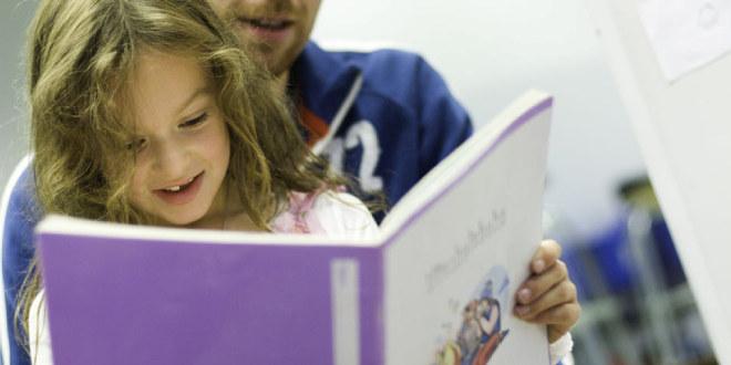 Illustrasjonsfoto av barnehagebarn som ser i en bok