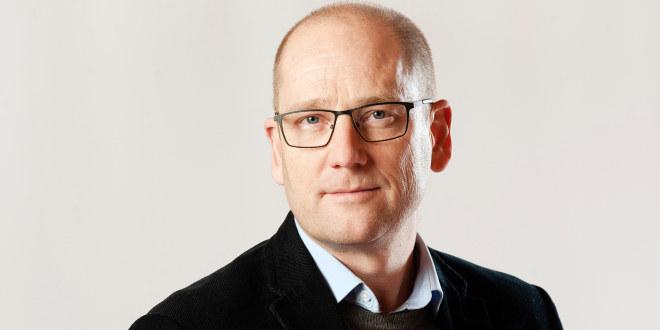 Skallet mann med briller, skjorte og sort genser. Nærbilde.