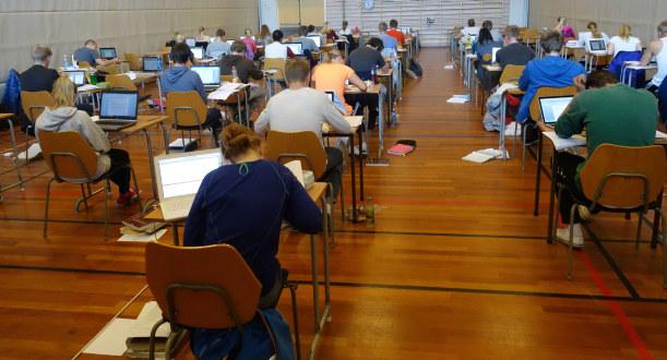 Elever sitter ved hver sin i en gymsal og skriver