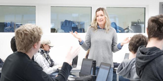 Lærer, dame, i grå genser med lyst hår snakker foran en klasse.