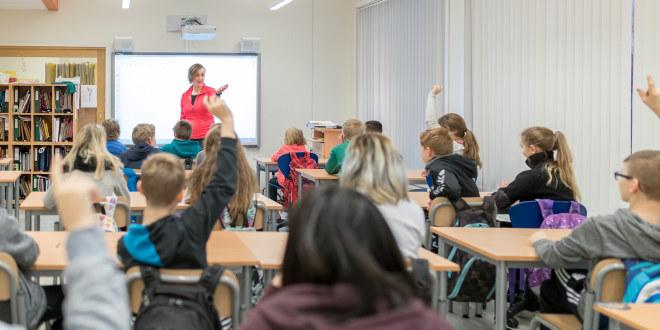 Elever sitter på pultene sine i et klassrom. Rekker opp hender.