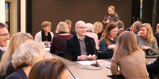 Flere mennesker sitter rundt møtebord.