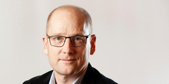 Steffen Handal med briller ser rett inn i kameraet med et halvlurt smil. Bakgrunnen er grålig hvit.