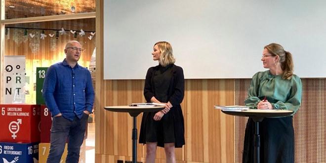 En mann og to damer står ved to runde bord og snakker til publikum.