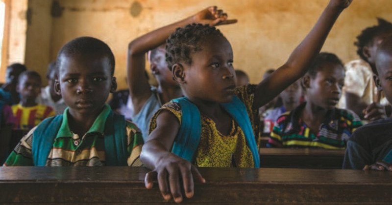 Barn i et klasserom som rekker opp hånden for å svare på spørsmål. Bildet er forsiden på en rapport om vold og angrep på skoler, elever og lærere.