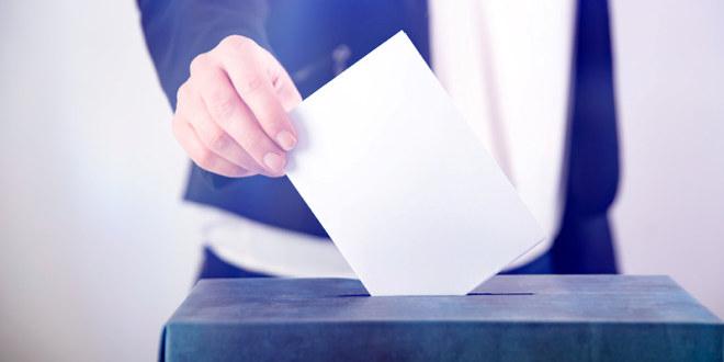 Hånd legger stemmeseddel opp i stemmeurnen.