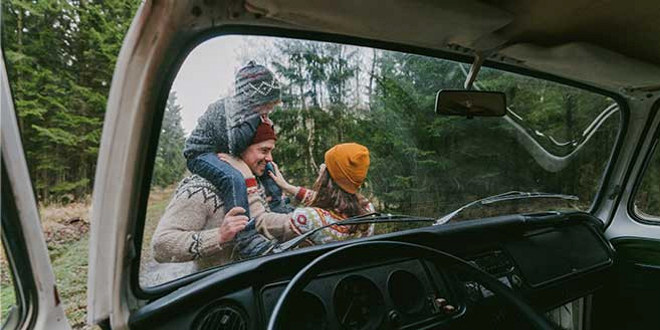 Bilde av mann, dame og barn ute foran en parkert bil
