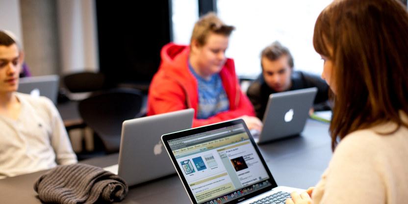 Fire elever som sitter ved bord og følger med på oppslåtte PCer.