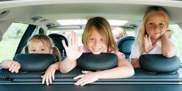 Bilde av tre barn som titter ut av bakvinduet på en bil