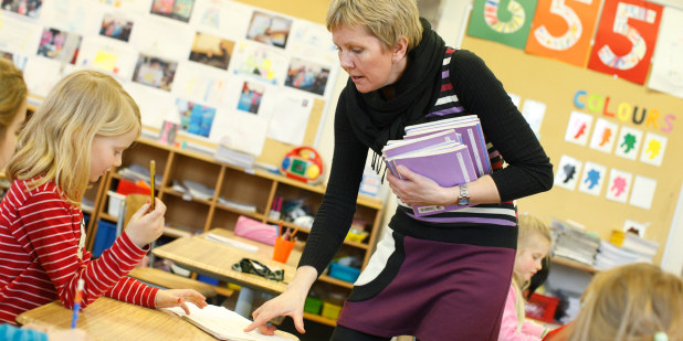 Lærer og barneskoleelever i et klasserom.