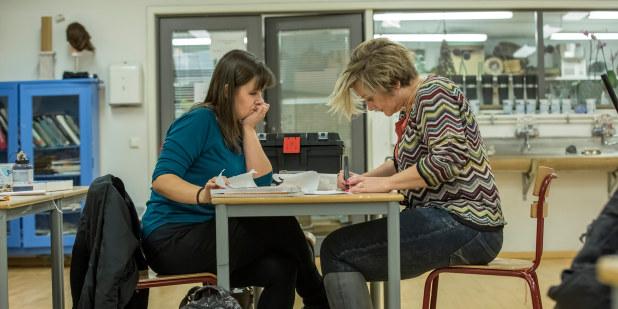 To damer som sitter ved et møtebord.