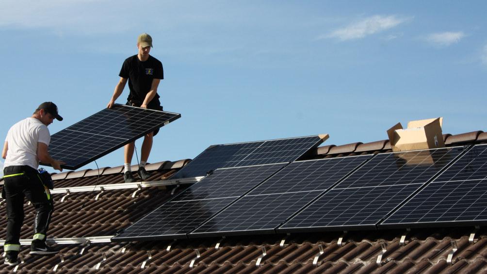 To montører setter et solcellepanel på taket til b-bygget i Utdanningsforbundets lokaler i Hausmannsgate 17 i Oslo